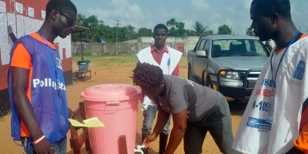 Liberians election workers watch as a voter washes her hands before casting her votes, during the senate...