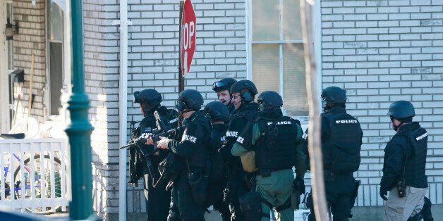 Police gather near a home, Monday, Dec. 15, 2014, in Souderton, Pa., where suspect Bradley William Stone...