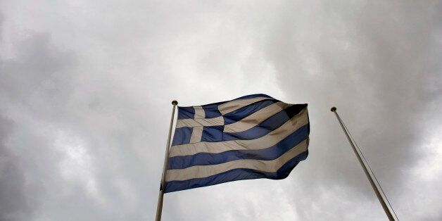 A Greek national flag flies from a pole beneath stormy skies outside the Hellenic Stock Exchange in Athens,...