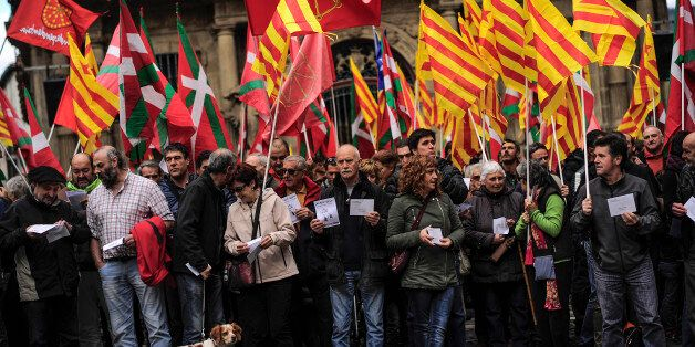 Pro-independence demonstrators of Catalonia and Basque Country raise their regional flags as they gather...