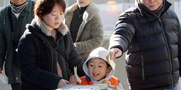 A boy (C) helps his mother (L) to cast a vote in Japan's general election at a polling station in Tokyo...