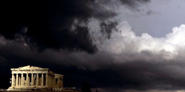 Dark clouds pass over a semi-sunlit Parthenon temple atop the ancient Acropolis Hill in Athens on Monday,...