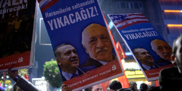 A Turkish protester holds up a placard with pictures of Turkish Prime Minister Recep Tayyip Erdogan (L)...