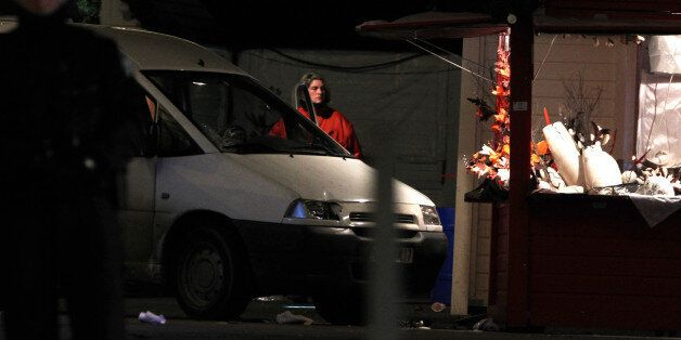 A police officer stands by the van that crashed into a French Christmas market in Nantes, western France,...