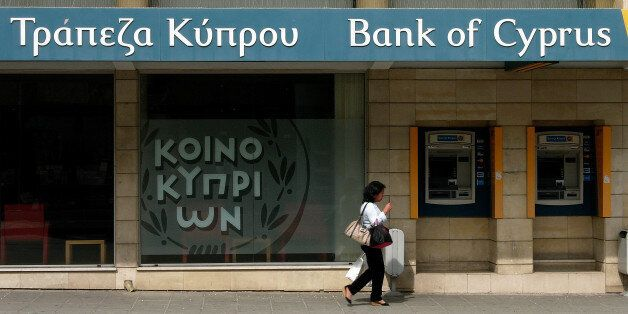 A woman passes outside a branch of Bank of Cyprus in the main shopping street in central capital Nicosia,...