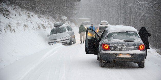 A car is stuck in the snow on December 27, 2014 on the road to Les Saisies ski resort in Savoie, central-eastern...