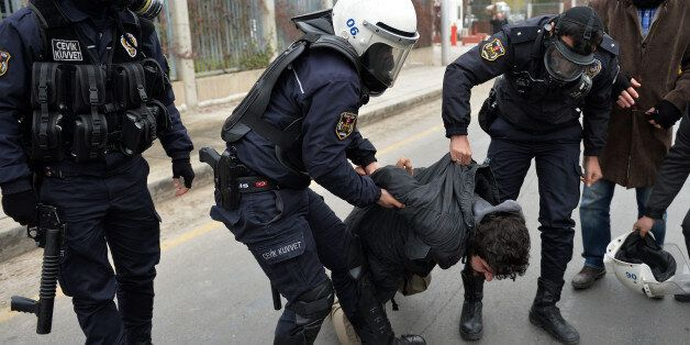 Riot police detain students after they used pepper spray to disperse a protest by dozens of students...