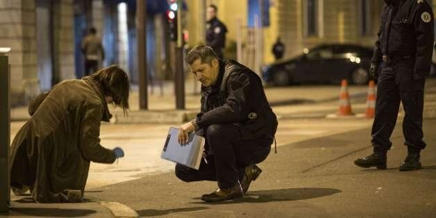 Policemen collect evidence on December 21, 2014 in Dijon on the site where a driver shouting 'Allahu...