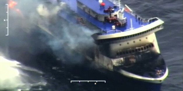 In this image taken from a video released by the Italian Coast Guard, smoke billows from the Italian-flagged...