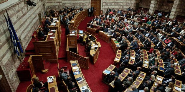 Greek Prime Minister Antonis Samaras, standing at podium, left, speaks to Parliament members during a...