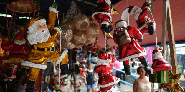 A Filipino woman looks at Santa Claus figurines outside makeshift stalls as people begin shopping for...