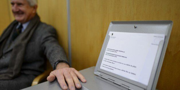 An usher guards the ballot box on November 30, 2014 in the old town of Fribourg. The Swiss voted early...