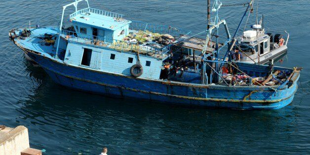 A boat carrying the bodies of dead migrants is towed into the Maritime base in Malta on July 20, 2014...