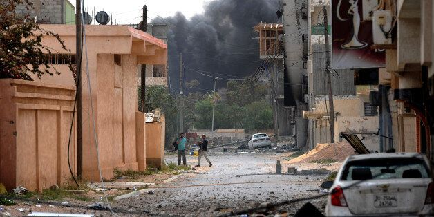 Libyan rebels are seen walking down a street close to a building where forces loyal to Col. Moamer Kadhafi...