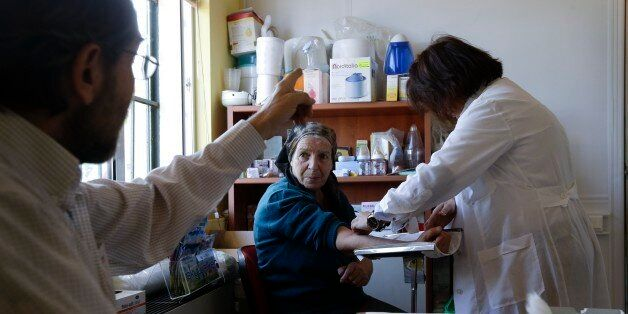In this photo taken Thursday, Nov. 13, 2014, a doctor gives instructions to an elderly woman as a nurse...