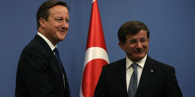British Prime Minister David Cameron, left, and his Turkish counterpart Ahmet Davutoglu shake hands after...