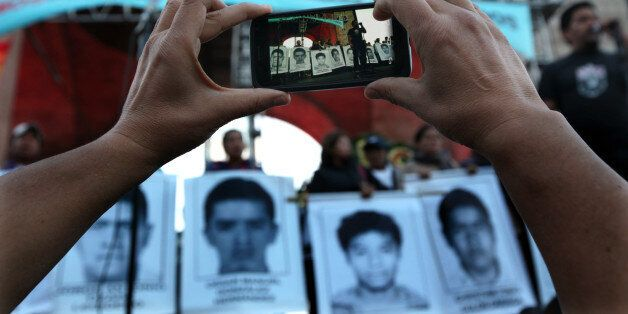 A protester takes a photo of the relatives of 43 missing students from the Isidro Burgos rural teachers...