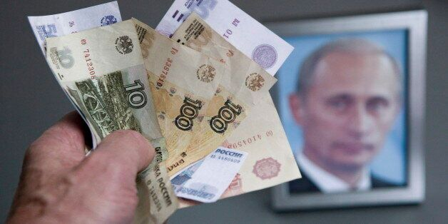 GERMANY, BONN - DECEMBER 02:Hand with russian ruble banknotes and a framed Putin photo in the background,...
