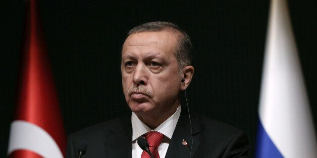 Turkish President Recep Tayyip Erdogan listens to his Russian counterpart Vladimir Putin during a joint...