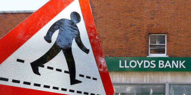 A pedestrian sign stands near a branch of Lloyds Bank in London, Tuesday, Oct. 28, 2014. The State-backed...
