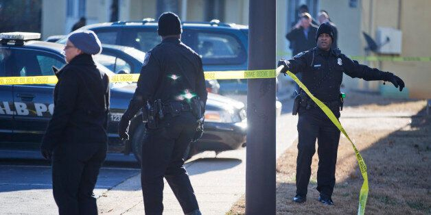 Police investigate the scene of an apartment complex where authorities say two officers were shot leading...