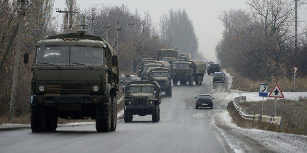 A military convoy of about 30 trucks without license plates coming from the east moves on the road on...