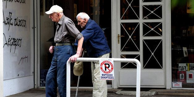 Two elderly men help one another on a sidewalk outside a bookstore in central Athens, Monday, June 2,...
