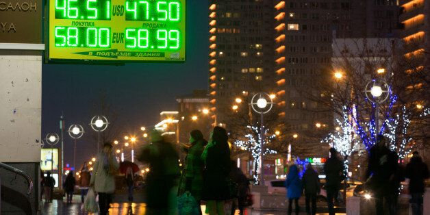 Pedestrians pass illuminated rates for dollar and euro currencies against the ruble on an electronic...