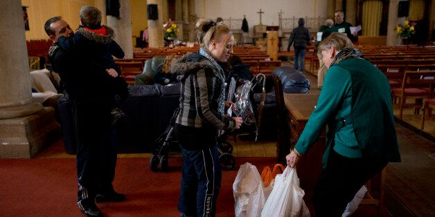 In this photo taken Friday, April 5, 2013, a volunteer, right, gives bags of food to Natalie Cribbin,...