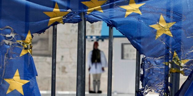 A Greek presidential guard stands as he seen through the remains of a European Union flag half-burnt...