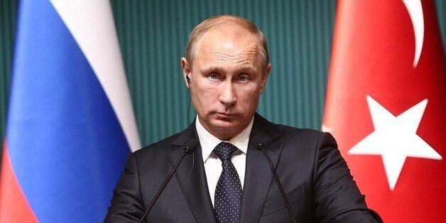 Russian President Vladimir Putin listens to a question as he speaks to the media during a joint news...