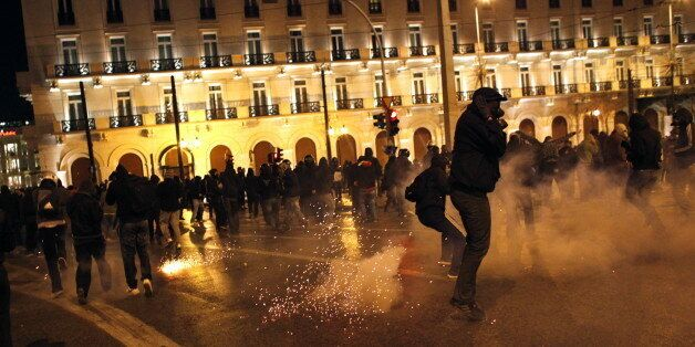 Protestors clash with riot police outside the parliament in Athens on December 6, 2011, during demonstrations...