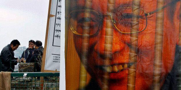 Exile Tibetans take refreshments at a parking lot where a portrait of imprisoned democracy activist Liu...