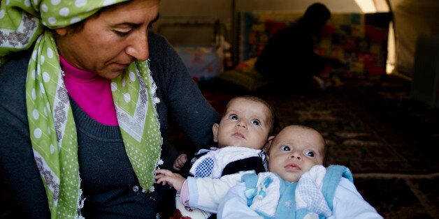 A Syrian Kurdish refugee woman from the Kobani area holds two babies at a camp in Suruc, on the Turkey-Syria...