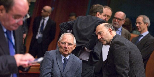 European Commissioner for Economic and Financial Affairs Pierre Moscovici, center right, speaks with...