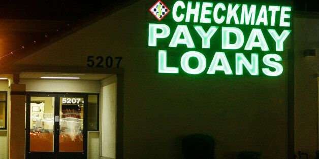 Neon signs illuminate a payday loan business in Phoenix on Tuesday, April 6, 2010, one of 650 operating...