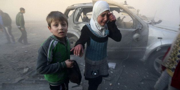 A girl cries near a damaged car at a site hit by what activists said were barrel bombs dropped by government...