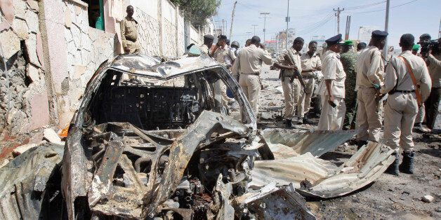Somali soldiers stand by wreckage at the scene of a suicide car bomb attack that targeted a United Nations...