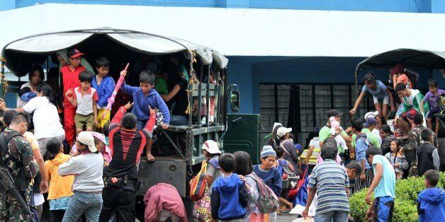 Residents are evacuated to a safer place in Legazpi City, Albay province, southeast of Manila on December...