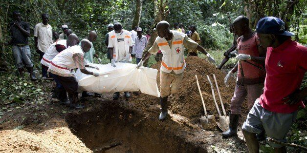 Health workers from Guinea's Red Cross carry the body of a victim of the Ebola virus in Momo Kanedou...