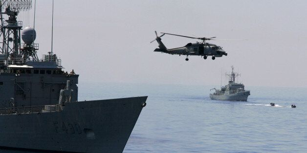 A Turkish Navy Blackhawk helicopter takes off from the Turkish frigate Gaziantep, left, as French Navy...