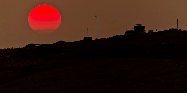A soldier walks at a Turkish military outpost overlooking the Syrian city of Kobani, on a hilltop outside...