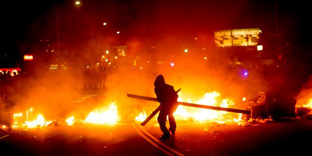 A protester adds wood to a fire burning in Oakland, Calif., on Tuesday, Nov. 25, 2014, a day after the...