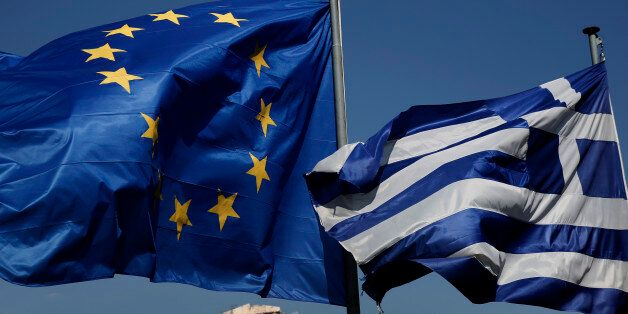 An EU and a Greek flag fly in front of the ancient Parthenon temple, in Athens, on Wednesday, April 9,...