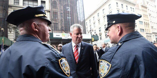 New York City Mayor Bill de Blasio (C) speaks with NYPD officers before a Veterans Day Parade in New...