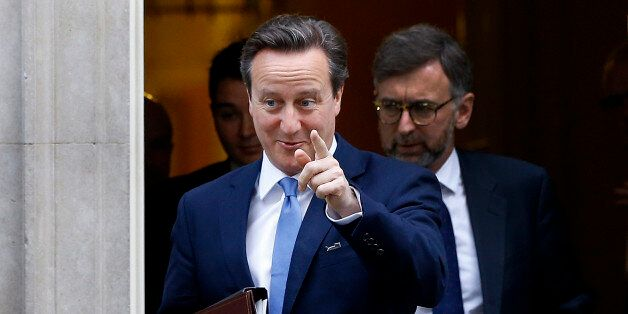Britain's Prime Minister David Cameron points towards the media as he leaves 10 Downing Street in London,...