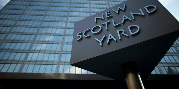A sign rotates outside New Scotland Yard, the headquarters building of London's Metropolitan Police force...