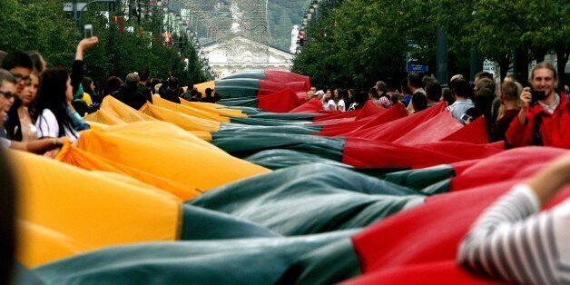 Lithuanians carry a 1000 metre long Lithuanian flag as they march during a celebration of the 25th anniversary...