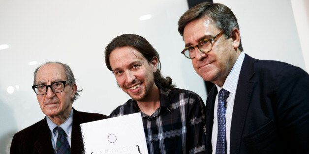 Pablo Iglesias, Secretary General of 'Podemos' ('We can'), center, poses as he holds 'An Economic Project...