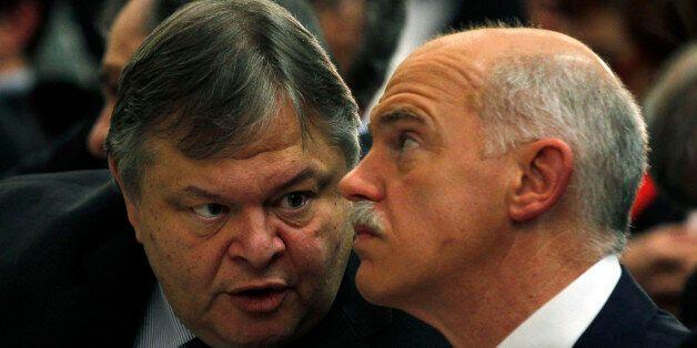 Greeces' Finance Minister Evangelos Venizelos, left, speaks to former Greek Prime Minister George Papandreou...